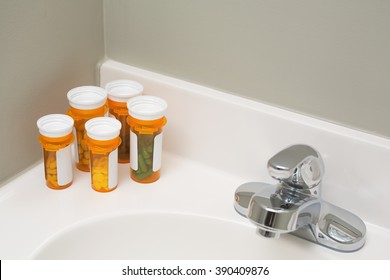 Prescription medicine bottles, with easy open caps, sitting on bathroom sink.