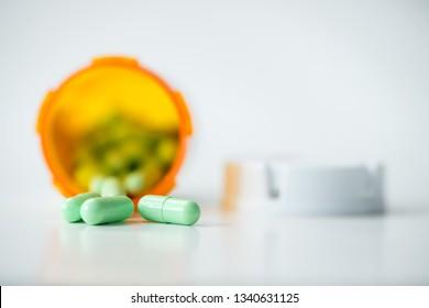 Prescription medicine green capsules cascading out of orange pharmacy bottle