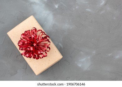 present box in craft paper with red bow on grey background with copy space