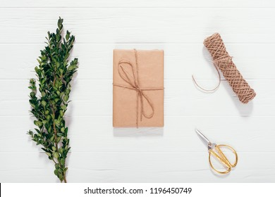Present box wrapped in brown paper on white wooden table next to branch of green boxwood, twine coil and golden scissors, top view. Scandinavian style Christmas gift arrangement, flat lay.