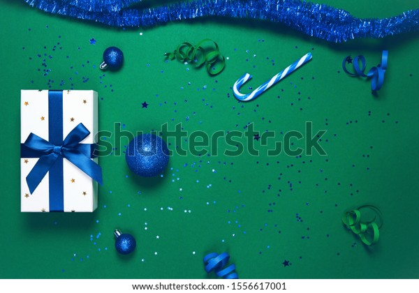 Present box wrapped with dark blue ribbon, decorative balls and lollipop on green paper background. Christmas gift.  Holiday concept. Image is with copy space. Flat lay. Top view