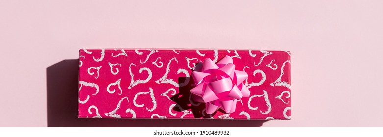 Present or gift box, paper heart and pink bow ribbon on pink background top view. Valentines day greeting card. Happy Valentine's day composition. Red gift box with hearts.copy space.