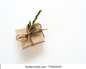 A present or gift box wrapped by rough brown recycled paper and tied with brown hemp rope ribbon with pine branch isolated on white background with concept of green and environment and nature friendly