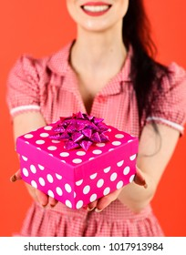 Present, gift, Womans day, Christmas, shopping, holiday concept. Girl with cheerful face and pink box. Woman in stylish dress holds present and smiles. Happy girl with gift isolated on red background.