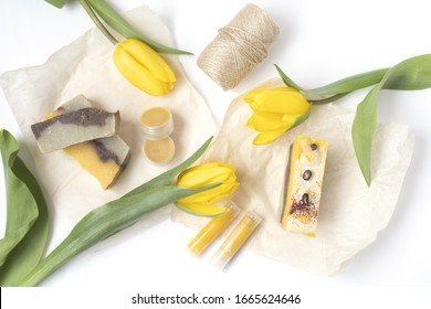 Present for international ladies day. Hand made soap, lip balm, beautiful tulips. White background. Top view. Flat lay. Natural cosmetics.