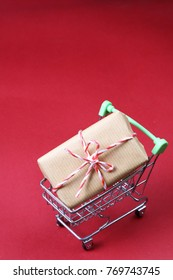 Present on mini trolley on red background