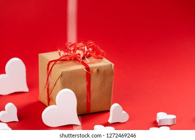 present on red background with white hearts and copy space