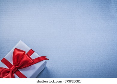 Present red ribbon on blue background greeting card holidays concept.
