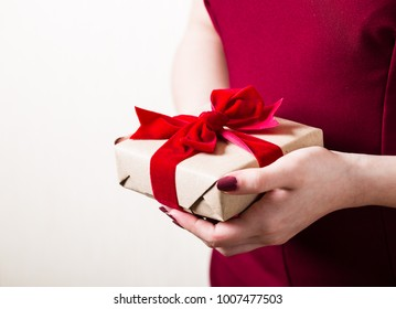 Present for Valentine`s day or birthday for a woman. Gift with red ribbon velour satin tied bow in female hands, red dress, light skin, copy space