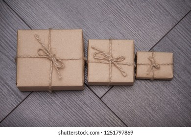 Present wrapped in craft paper with sack rope on wooden background. Smaller or bigger concept.