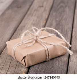 Present wrapped in plain brown paper and tied with string on a rustic wood surface