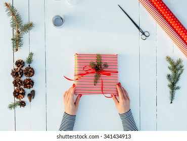 Present wrapped in red paper on a wooden background with a red ribbon for christmas, birthday, mother's day or valentine