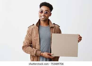 Present for you. Isolated on white portrait of young fashionable dark-skinned man with afro hairstyle in grey t-shirt, brown jacket and sun-glasses holding box in hand, smiling in camera