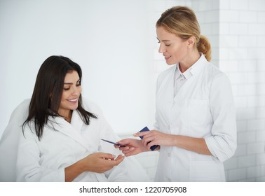 Present for you. Portrait of charming woman in white bathrobe lying on daybed and reaching out hand while cosmetologist giving face cream samples