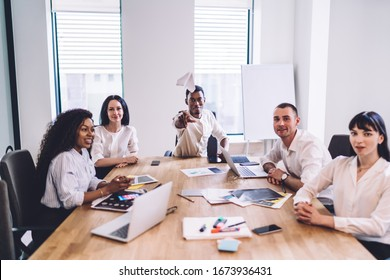Presentable African American employee sitting in bright office and playing with paper airplane while joyful and happy colleagues looking at camera