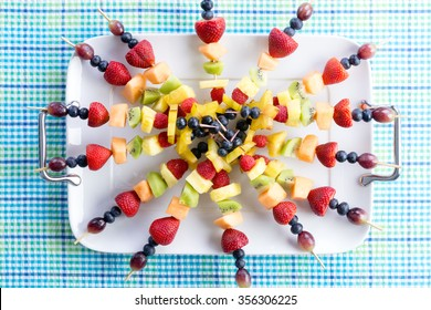 Presentation of colorful healthy fresh fruit kebabs on a summer picnic table made with seasonal exotic and tropical fruit for a gourmet dessert, overhead view