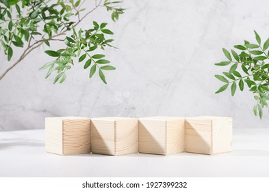 Presentation and display product - wooden cube podiums in row with green branch of tree in sunlight on white wood board and grey marble wall. - Shutterstock ID 1927399232