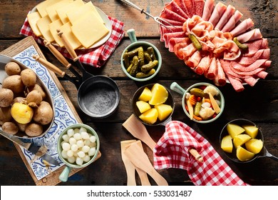 Presentation of fresh ingredients for making raclette with a platter of cold meats, potatoes, sliced Swiss cheese and assorted diced vegetables and pickles, overhead view