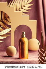 presentation of golden perfume bottle next to geometric shapes and palm leaves