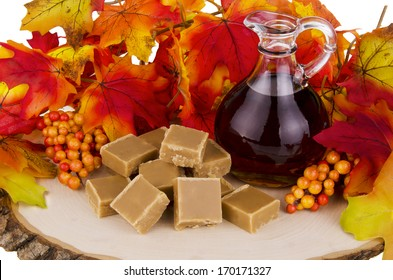 Presentation of maple syrup and sugar cream fudge on wooden plate.