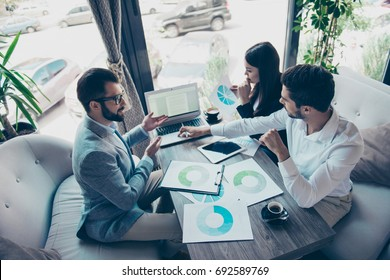 Presentation of a new start up for investors. Three young successful people are discussing numbers in a nice light modern coworking, all in formal wear, concentreted
