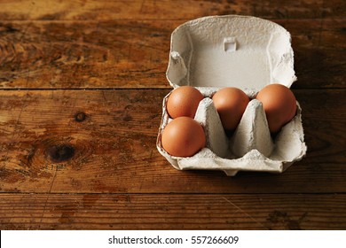 Presentation of opened recyclable egg carton for six eggs containing four big ecological eggs on a aged vintage rustic brown wooden table