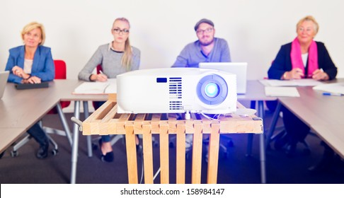 Presentation projector with an audience in a conference room in the background