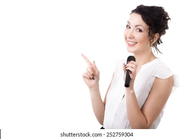 Presentation, public speech, conference, broadcasting, advertising. Young businesswoman, reporter, media presenter holding microphone, pointing on copyspace, isolated