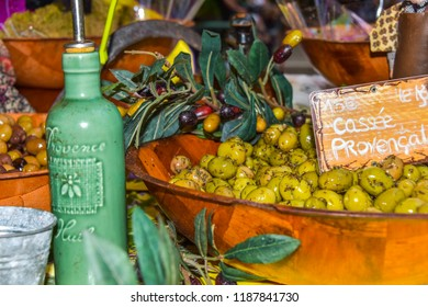 presentation of regional products, olives with herbs and olive oil of the Provence, decoration with olive branches, Riez, France, stall at the street market on the annual festival of lavender honey
