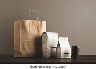 Presentation of retailer package set: craft paper bag, big pouch, small container and take away glass with cap. Filled with goods, blank labeled, merchandise pack
