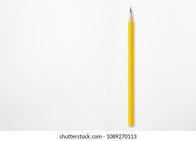 Presentation template with copy space by top view close up macro photo of wooden yellow pencil isolated on white paper that look minimalist and clean.Flash light made smooth shadow from yellow pencil.