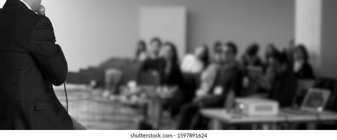 Presenter at corporate conference giving speech. Speaker giving lecture to business audience in seminar. Executive manager leading discussion in hall during company training event.