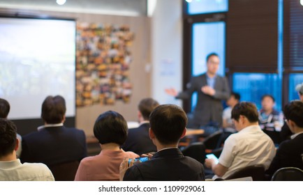 Presenter with Hands Pointing. Blurred De-focused. Unidentifiable Business Audience People Meeting in Conference Room. Speaker in Lecture. MBA Phd Teacher Giving Speech.
