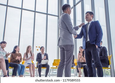 Presenter introducing new friend and co worker ,workshop group of young cheerful people sitting on conference together and applauding