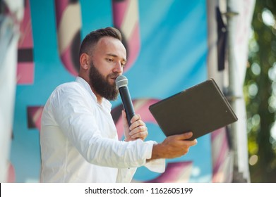 Presenter with microphone. Emcee definition is - master of ceremonies