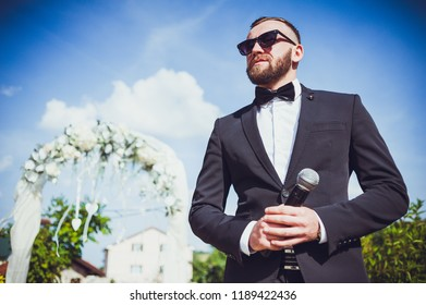 Presenter on stage with microphone. Wedding MC. Toastmaster.