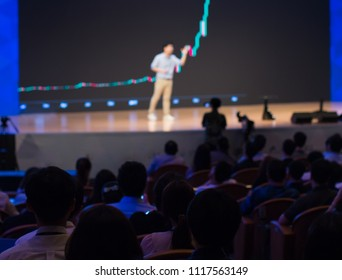 Presenter Presenting on Stage at Conference Hall Exhibition. Professional Lecture. Growth and Technology. Chart on Screen. Blurred De-focused Unidentifiable Presenter and Audience.