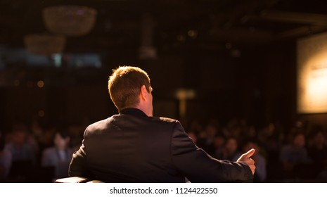 Presenter Presenting on Stage at Conference Hall Meeting Panel. Professional Lecture. Blurred De-focused Unidentifiable Presenter and Audience. Corporate Executive Manager Speaker Teacher. People
