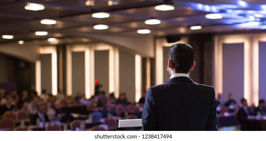 Presenter Presenting Presentation to Audience. Defocused Blurred Conference Meeting People. Lecturer on Stage. Speaker Giving Speech to Audience in Conference Hall Auditorium. Forum for Professionals