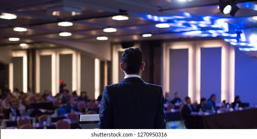 Presenter Presenting Presentation to Audience. Defocused Blurred Conference Meeting People. Lecturer on Stage. Speaker Giving Speech to People.