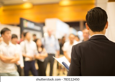 A Presenter Presents to Group of People in Nice Building with Good Lighting.
