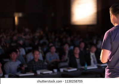 Presenter Speaking to Audience People in Conference Hall Auditorium. Presentation Stage. Blurred De-focused Unidentifiable Audience and Presenter. Technology. Casual Attire Presenter.