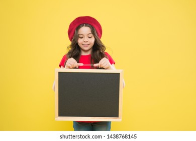 presenting product. small girl kid with school backboard, copy space. back to school. advertising board for promotion. school shopping sales. child on yellow background. happy girl in french beret.