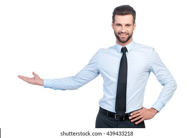Presenting something special. Confident young handsome man in shirt and tie pointing away and smiling while standing against white background