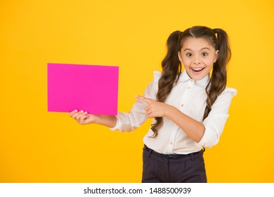 Presenting your product. Happy little girl pointing finger at blank pink paper for product advertising on yellow background. Back to school product. Drawing attention to product or event, copy space.