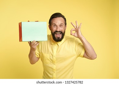 presenting your product. happy man hold shopping bag and presenting product. copy space play for presenting product. man with ok gesture presenting product
