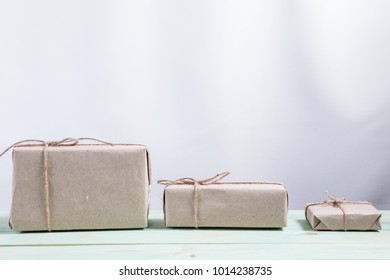 Presents for any holiday concept. Border of decorative gifts wrapped kraft paper tied with tourniquet for christmas, valentine day or birthday