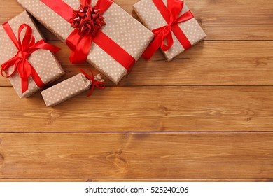 Presents for any holiday concept. Gift boxes frame, top view with copy space on wood table surface background. Border of packages with red satin ribbons for christmas, valentine day or birthday