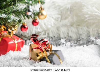 Presents lying in the fake snow under the Christmas  tree