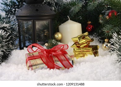 Presents lying in the fake snow under the Christmas tree and a white candle  is standing near the lantern in the background